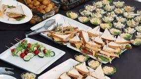 Участники конференции завербовывают еду на очень вкусной таблице шведского стола r акции видеоматериалы