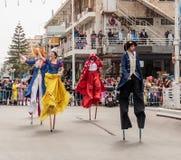 Участники на масленице на ходулях идут вдоль улицы Стоковая Фотография