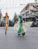 Участники на масленице на ходулях идут вдоль улицы Стоковые Изображения
