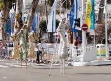 Участники на масленице на ходулях идут вдоль улицы Стоковое Изображение