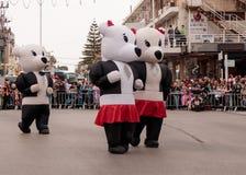 Участники одетые в больших раздувных костюмах идут вперед Стоковые Фото