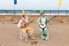 Участники фестиваля одетые как клоуны играя зашнурованное inst Стоковые Изображения