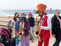 Участники фестиваля одетые как клоуны играя музыкальное instr Стоковое Фото