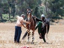 Участник в реконструкции рожков сражения Hattin в 1187 сидит на воюя лошади, и второе помогает ему на wa Стоковые Фото
