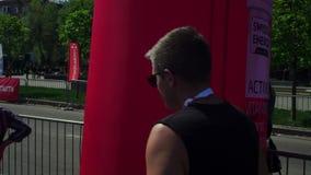 Участник марафона, молодой парень, спортсмен, в солнечных очках, после бега, идя вдоль следа, через город видеоматериал