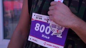 Участник марафона, после бега, отдыхает Он касается медали для метра 1 кило Его рубашка имеет его сток-видео