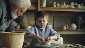 Учащийся гончарни мальчика создает clayware на бросать-колесе пока его опытное grandgather говорит к нему сток-видео