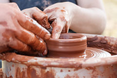 Уча гончарня ` S carftman вручает направлять руку ребенка, показывая как бросить глиняный горшок на колесе гончаров стоковые фото