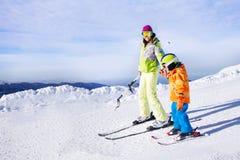 Уча мальчик, который нужно кататься на лыжах идущ держащ руку Стоковые Фотографии RF