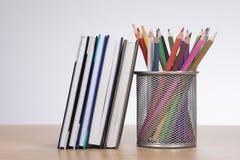 Учебники с комплектом покрашенных crayons карандаша Стоковая Фотография