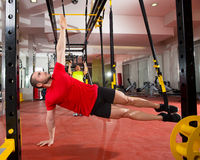 Учебные упражнени пригодности TRX на женщине и человеке спортзала Стоковые Изображения RF