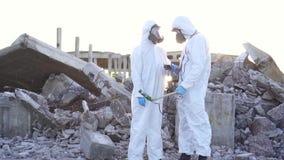 2 ученого в защитных костюмах и масках и сделать измерения радиации на фоне руин на акции видеоматериалы