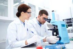 Ученые с доской сзажимом для бумаги и микроскопом в лаборатории Стоковое фото RF