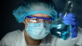 Ученый анализируя голубую прозрачную жидкость в склянке, проверке тяжелых металов воды стоковые фото