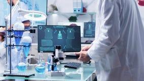 Ученый в белом пальто использует цифровой ПК планшета после этого случается на его столе видеоматериал