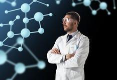 Ученый в пальто лаборатории и изумлённые взгляды с молекулами стоковая фотография