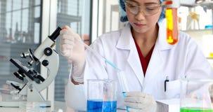Ученый делая эксперимент в лаборатории сток-видео