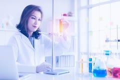 Ученый держа оранжевую жидкость в пробирке стоковые фото