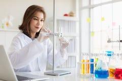 Ученый держа оранжевую жидкость в пробирке стоковые изображения