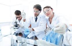 Ученый держа пробирку или некоторое оборудование науки стоковые изображения rf