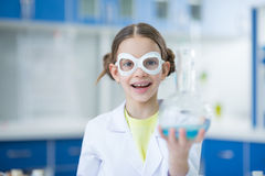 Ученый девушки в защитных стеклах держа склянку и усмехаясь на камере Стоковая Фотография RF