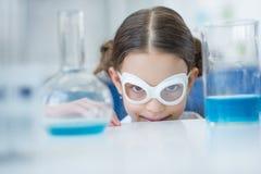 Ученый девушки в защитных стеклах усмехаясь на камере в лаборатории Стоковое Изображение