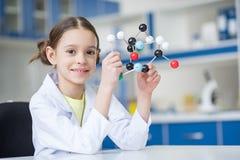 Ученый девушки в пальто лаборатории держа молекулярные модель и усмехаться Стоковое фото RF