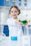 Ученый девушки держа склянку с реагентом и усмехаясь на камере Стоковое фото RF