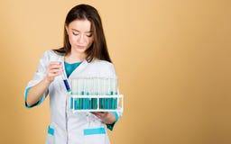 Ученый женщины в лаборатории r доктор женщины с испытывая трубкой и микроскопом, исследованием Лаборатория школы биологии стоковые изображения rf
