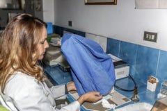 Ученый женщины осторожно покрывает микроскоп после использования его, в середине лаборатории стоковые фотографии rf
