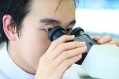 Ученый используя микроскоп на работе в лаборатории Стоковые Фотографии RF