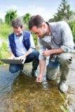 Ученый и биолог работая совместно на анализе воды Стоковая Фотография