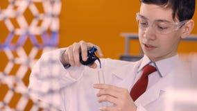 Ученый мальчика подсчитывает голубые падения понижаясь от склянки в стеклянную лампу 4K сток-видео