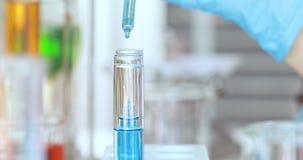 Ученый падая голубая жидкость в пробирки видеоматериал