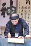 Ученый пишет китайские характеры каллиграфии на виске литературы Стоковые Изображения