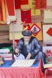 Ученый пишет китайские характеры каллиграфии на виске литературы Стоковое Фото
