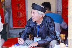 Ученый пишет китайские характеры каллиграфии на виске литературы Стоковые Изображения RF