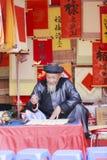 Ученый пишет китайские характеры каллиграфии на виске литературы Стоковое фото RF