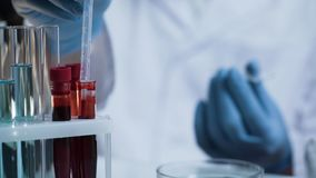 Ученый принимая падение крови для медицинского исследования, создавая вакцину, нововведение стоковое изображение rf
