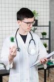 Ученый проводит эксперименты с зеленым растением стоковое фото