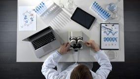 Ученый работая на компьютере и микроскопе в лаборатории, взгляд сверху исследования стоковая фотография