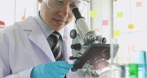 Ученый регулируя микроскоп для эксперимента сток-видео