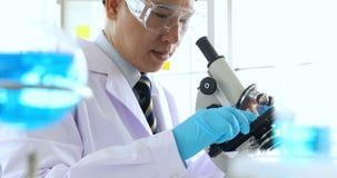 Ученый регулируя микроскоп для эксперимента видеоматериал