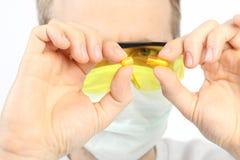 Ученый с 2 половинами оранжевой капсулы в его руке на белой предпосылке Стоковые Изображения