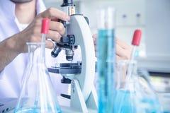 Ученый ученого смотрит через микроскоп, в комнате лаборатории стоковое изображение