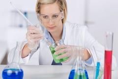 Ученый экспериментируя на столе в лаборатории Стоковое Изображение RF