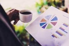 Учет коммерческих операций анализа бизнесмена Рука держа кофе c стоковые изображения