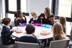 Учительница вставая на колени для того чтобы поговорить с группой в составе дети начальной школы сидя совместно на круглом столе  стоковые изображения rf