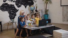 Учительница с его компьтер-книжкой малой потехи студентов наблюдая на классе землеведения в начальной школе Учитель и дети акции видеоматериалы