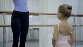 Учительница учит маленькой девочке в школе балета сток-видео
